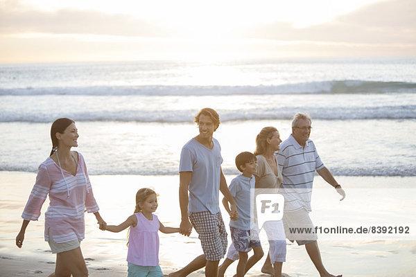 Mehrgenerationen-Familie beim gemeinsamen Spaziergang am Strand