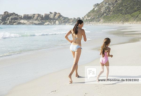 Mutter und Tochter beim Laufen am Strand