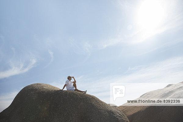 Mann auf einer Felsformation sitzend