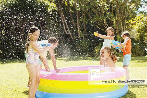 Vater und Kinder beim Spielen mit Wasserpistolen im Hinterhof