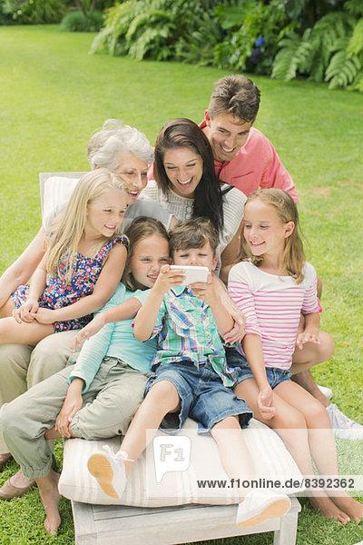 Familie  die zusammen im Garten ein Handy benutzt
