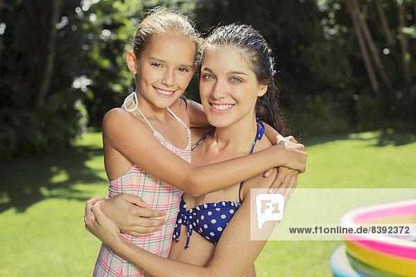 Mother and daughter hugging in backyard