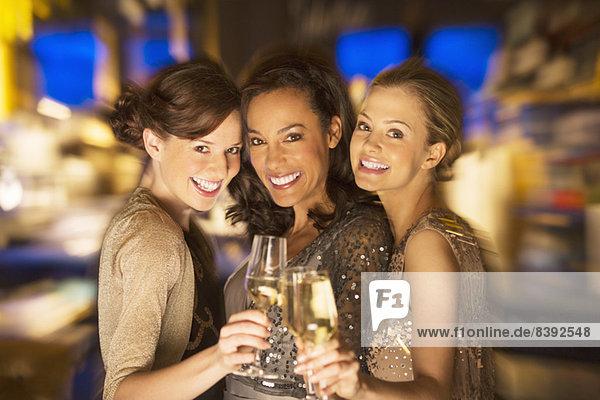 Lächelnde Frauen toasten Champagnergläser im Nachtclub