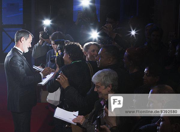Prominente geben Autogramme auf rotem Teppich