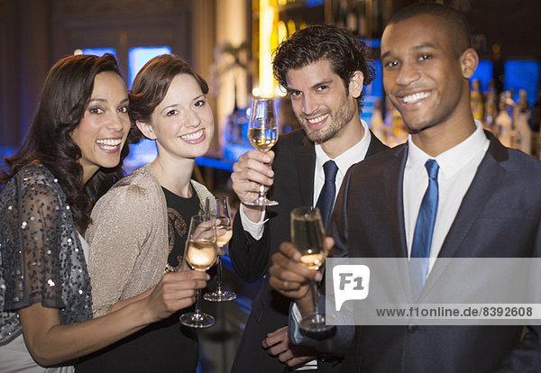 Porträt von gut gekleideten Paaren  die auf Champagnerflöten anstoßen.