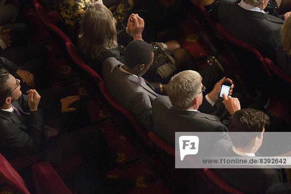 Mann mit Handy im Theaterpublikum