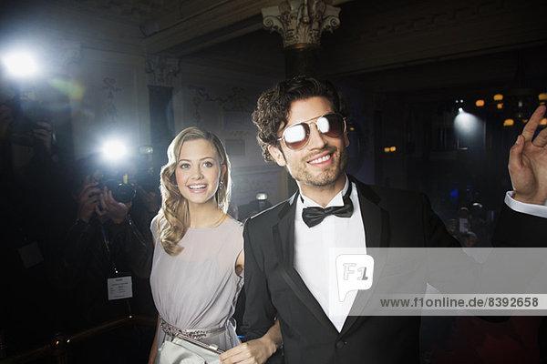 Gut gekleidetes Prominentenpaar winkt Paparazzi auf rotem Teppich zu