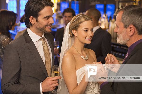 Vater hält Brauthände beim Hochzeitsempfang