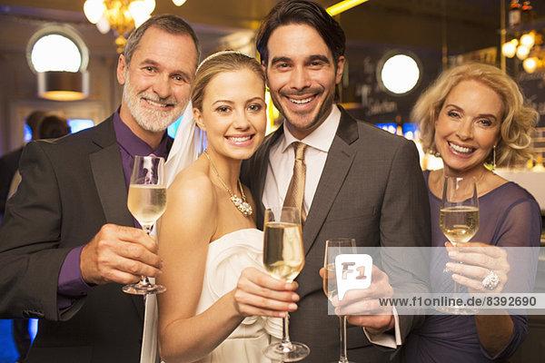 Porträt der glücklichen Braut und des Bräutigams beim Toasten von Champagnerflöten mit den Eltern