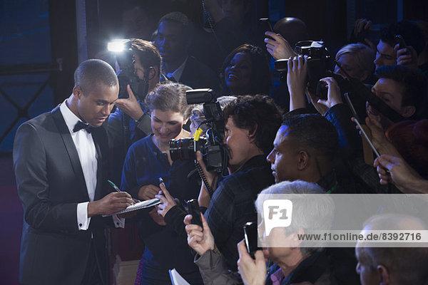 Gut gekleidete männliche Prominente geben Autogramme auf dem Roten Teppich