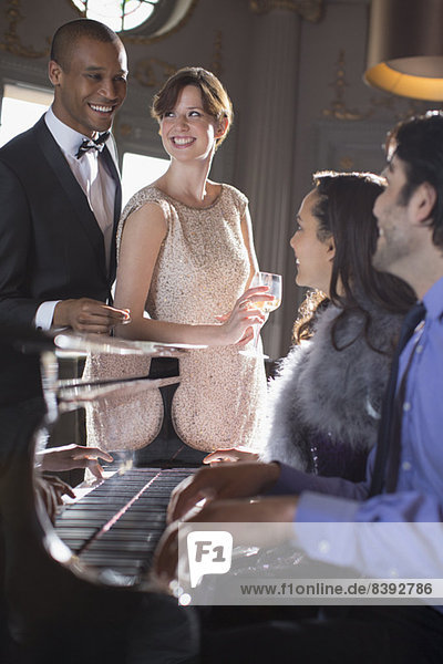 Gut gekleidete Freunde beim Klavierspielen in der Lounge
