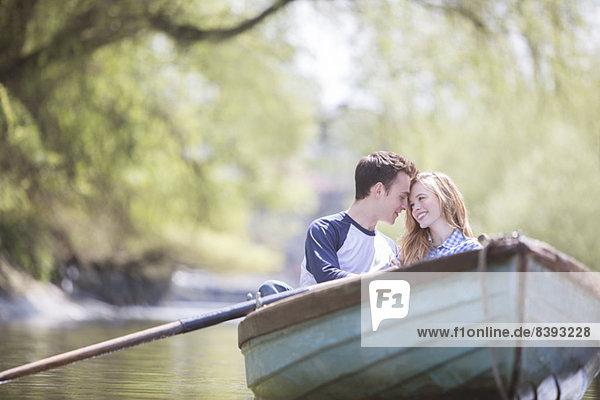 Paar sitzend im Ruderboot auf dem Fluss