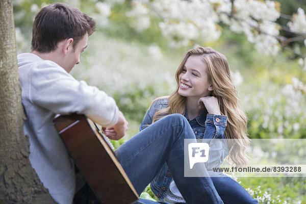 Mann spielt Gitarre für Freundin im Freien
