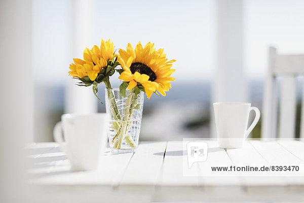 Vase mit Blumen und Kaffeetassen auf dem Küchentisch