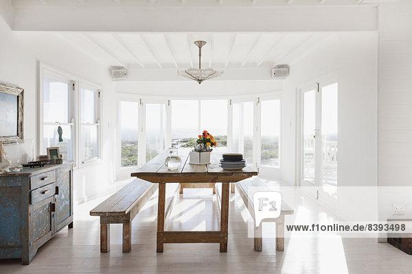 Holztisch und Bänke im sonnigen Esszimmer