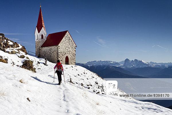 Wanderer bei der Bergkirche Latzfonser Kreuz  hinten die Dolomiten mit Langkofel  Plattkofel und Sellastock  Eisacktal  Südtirol  Italien