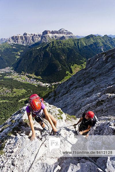 Bergsteiger beim Aufstieg über den Klettersteig Via ferrata dei Finanzieri zum Gipfel des Colàc im Fassatal  Val di Fassa  unten das Dorf Alba  hinten das Pordoijoch und der Sellastock  Dolomiten  Trentino  Italien