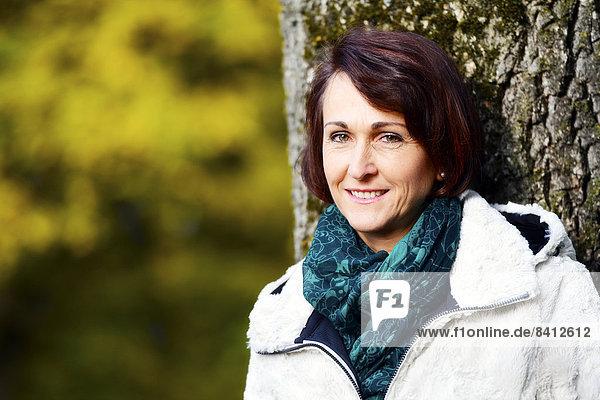 Lächelnde Frau an einem Baum im Herbst
