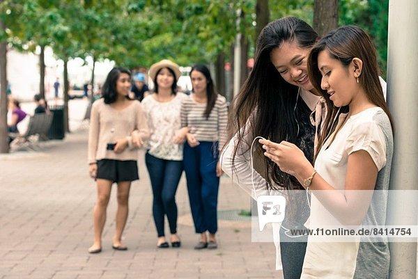 Frauen schauen auf Technik  Freunde kommen