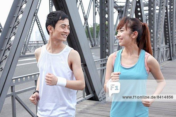 Junger Mann und junge Frau joggen über die Brücke