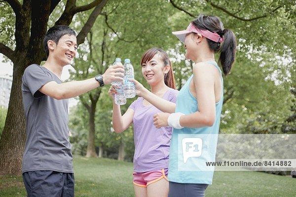 Joggerfreunde teilen sich das Wasser im Park