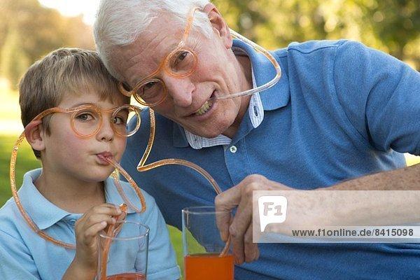 Großvater und Enkel trinken durch Strohbrille