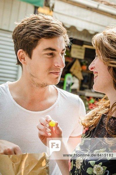 Junges Paar  das sich eine Tüte Essen teilt