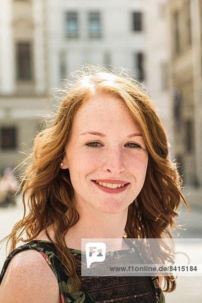 Porträt einer jungen Frau  die in der Stadt steht.