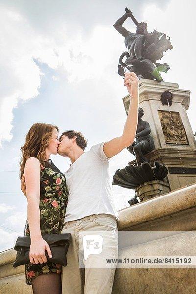Junges Paar neben Statue  Küssen und Selbstporträtfotografie Junges Paar neben Statue, Küssen und Selbstporträtfotografie