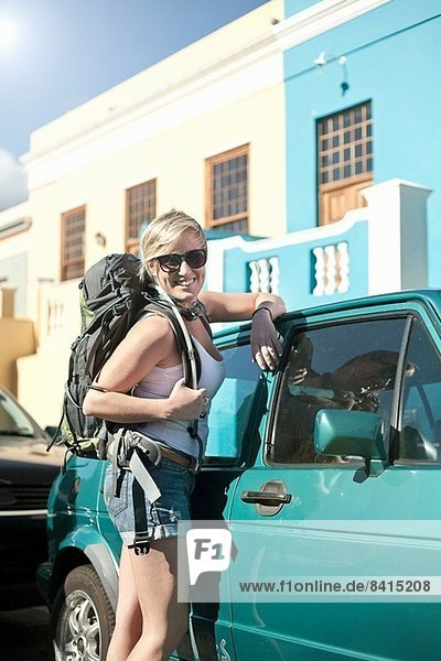 Young woman carrying backpack  leaning against car