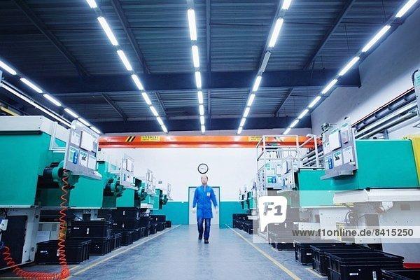 Arbeiter geht durch die Kleinteilefabrik in China