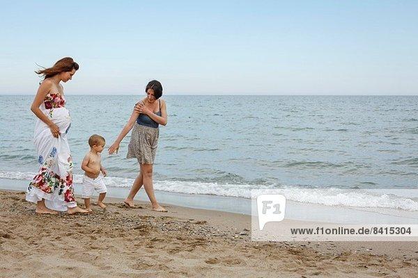 Frauen und Kleinkinder gehen am Ufer entlang