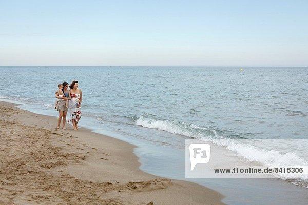 Frauen  die mit dem Arm am Ufer entlanggehen  eine Schwangere  die ein Kleinkind trägt.
