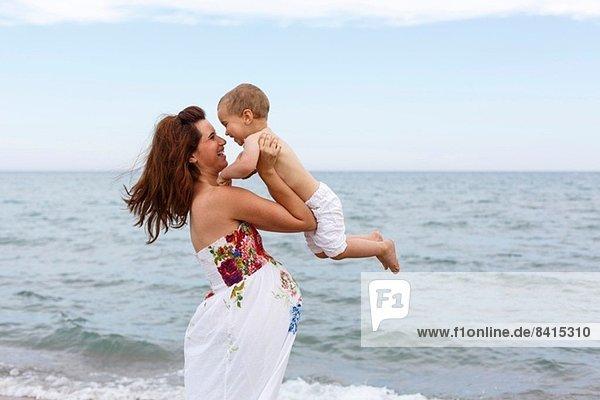Schwangere Frau hebt Kleinkind am Strand an