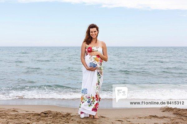Schwangere Frau am Strand stehend  Hände auf dem Bauch