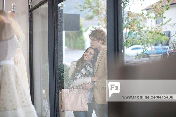 Junges Paar beim Schaufensterbummel  Blick durch die Ladenfront