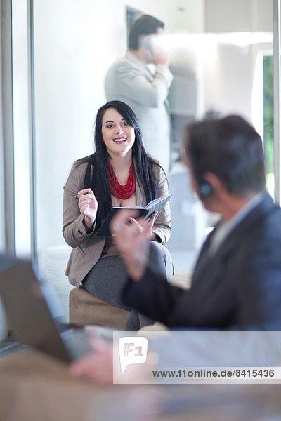Geschäftsmann mit Laptop  Geschäftsfrau beim Schreiben