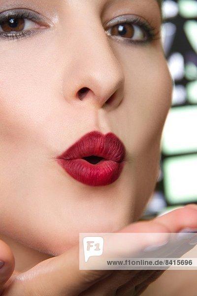 Ausgeschnittenes Studioporträt einer jungen Frau  die einen Kuss bläst.