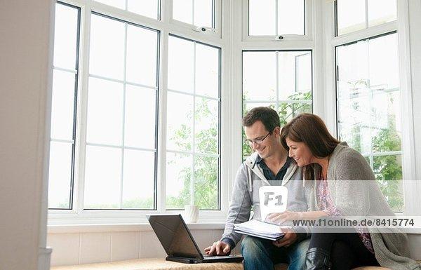 Paar auf Fenstersitz  mit Laptop