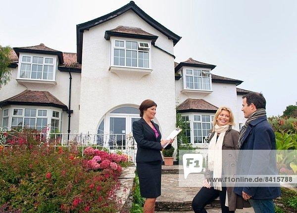 Mittleres erwachsenes Paar und Immobilienmakler außerhalb des Hauses
