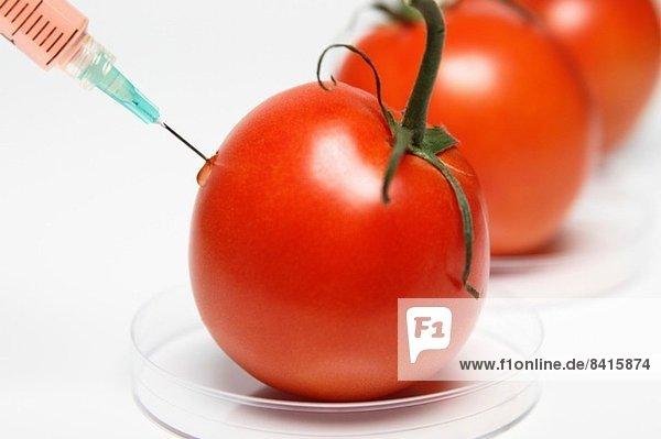 Lebensmittelforschung: Spritze zum Einspritzen von roter Flüssigkeit in eine Tomate