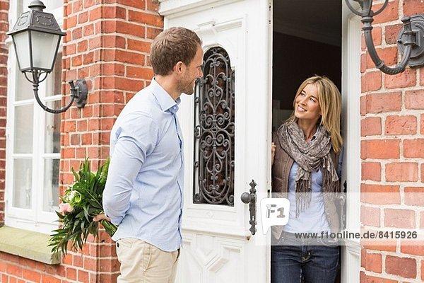 Mittleres erwachsenes Paar  Frau beim Öffnen der Haustür