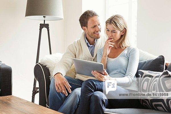 Mittleres erwachsenes Paar mit digitalem Tablett