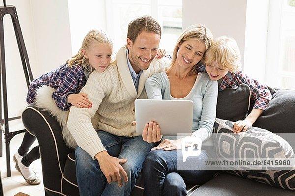 Eltern mit zwei Kindern mit digitalem Tablett