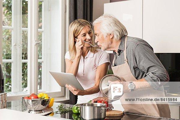 Älterer Mann kocht mit seiner Tochter  probiert Essen