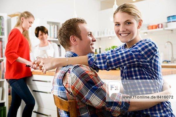Junges Paar in der Küche mit Frau und Teenagermädchen
