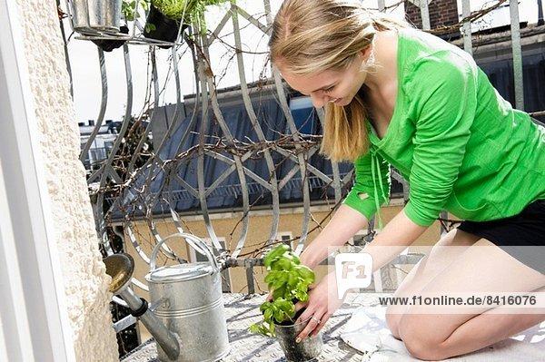 Teenagermädchen auf Balkon mit Topfpflanze