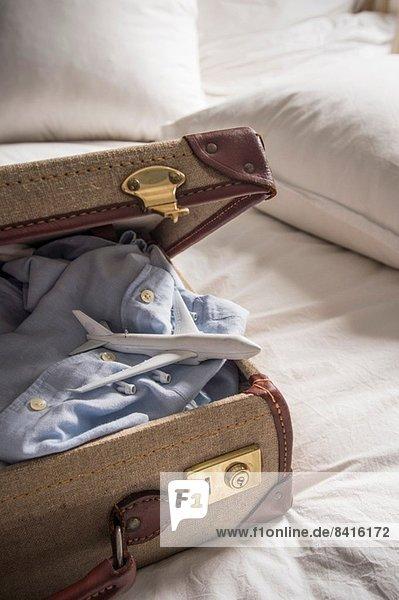 Offener Koffer am Bett mit Hemd und Spielzeugflugzeug Offener Koffer am Bett mit Hemd und Spielzeugflugzeug