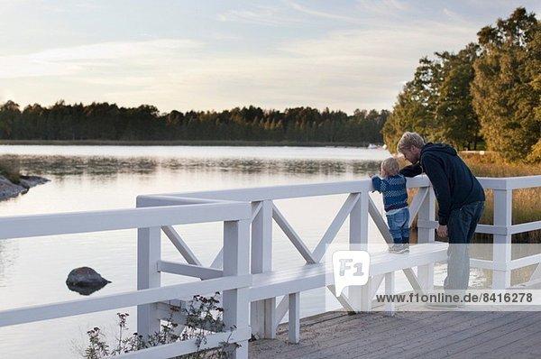 Vater und Sohn schauen auf den See