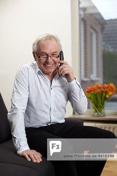 Älterer Mann zu Hause im Gespräch mit dem Handy
